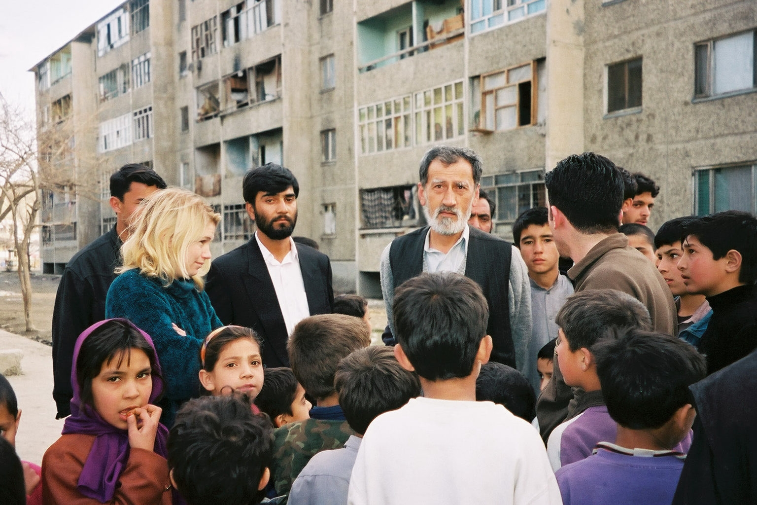 Four adults stand in front of a crowd of children in Kabul. There is a grey apartment building behind them.