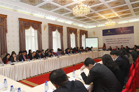 A conference in Mongolia depicts an ornate room. Tables with satin white tablecloths circle the room and people wear suits around the rectangle. A poster hangs on the wall.