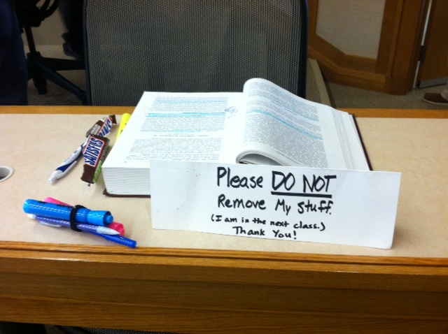 "a textbook, a bare candy wrapper, and some pens sit at a desk. in front of the desk there is a tent card that reads, ""please do not remove my stuff. I am in the next class. thank you"""