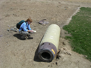 Bonnie Docherty examines a shell from a cluster munition in Iraq