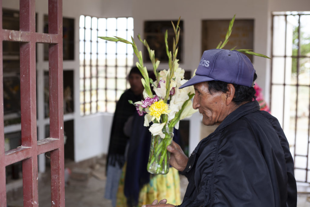 Teófilo Baltazar places flowers on the tomb of his wife, Teodosia, who was shot and killed during Black October.