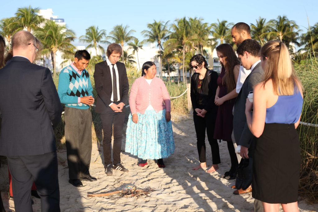 Plaintiffs, students, and staff stand around kindling on the beach to give thanks prior to the appeal.