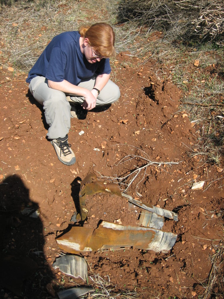 A woman kneals in the dirt examining the remainder of a cluster munition. It looks like broken stone buried in mud.