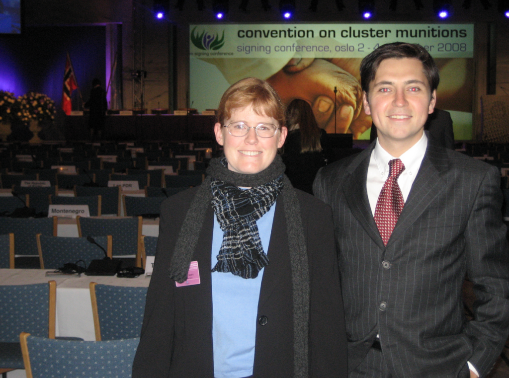 "Bonnie, a woman with red hair, stands next to her student, Chris, both of whom wear formal wear. They stand in front of a banquet room with a slide behind them that notes ""Convention on Cluster Munitions,"" and that it is the signing conference."