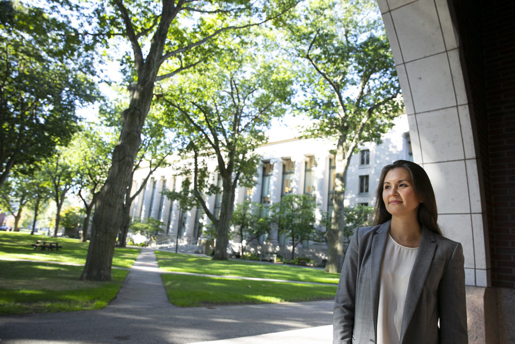 A woman wearing a gray blazer looks out into the distance under an arch in front of the Harvard Law library.