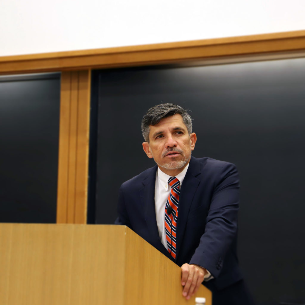 Victor Madrigal-Borloz stands in front of a podium in Wasserstein Hall. He wears a suit and tie and is speaking. He stands in front of a chalkboard.